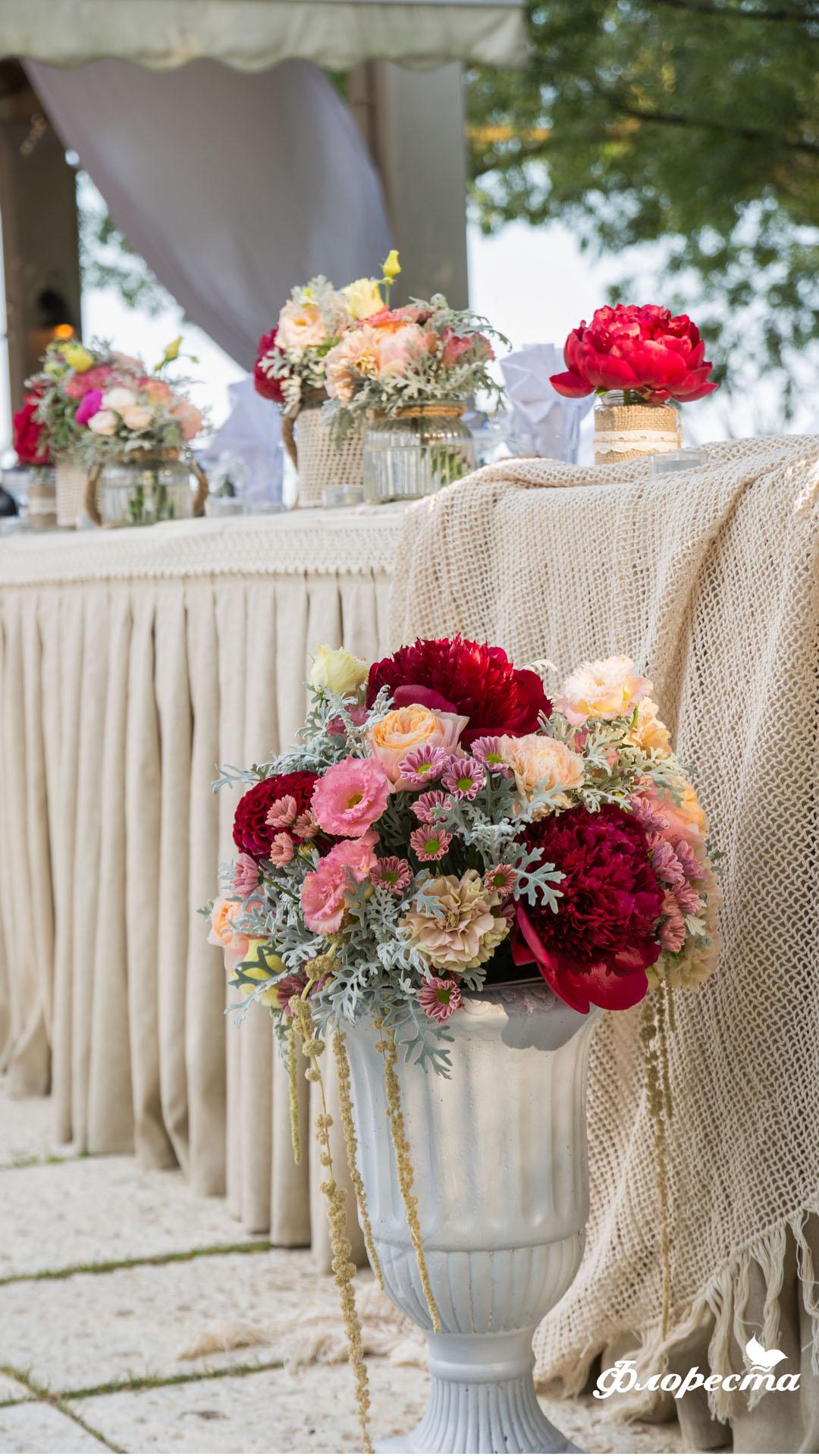 Цветна аранжировка пред масата на младоженците