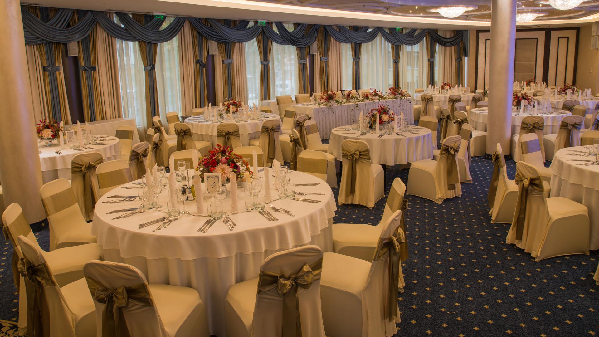 Сватбена декорация в злато на масите за гости в ресторант