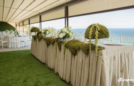 Празнична декорация на масата на младоженците в горско зелено