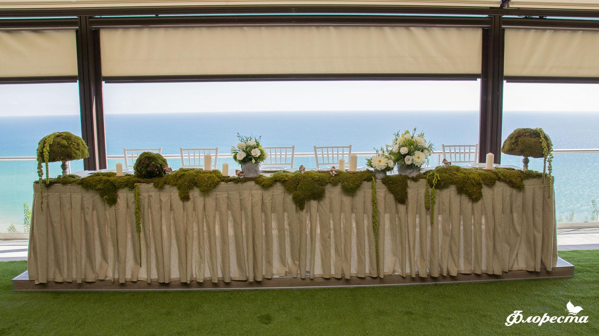 Сватбена декорация на масата младоженците в горско зелено