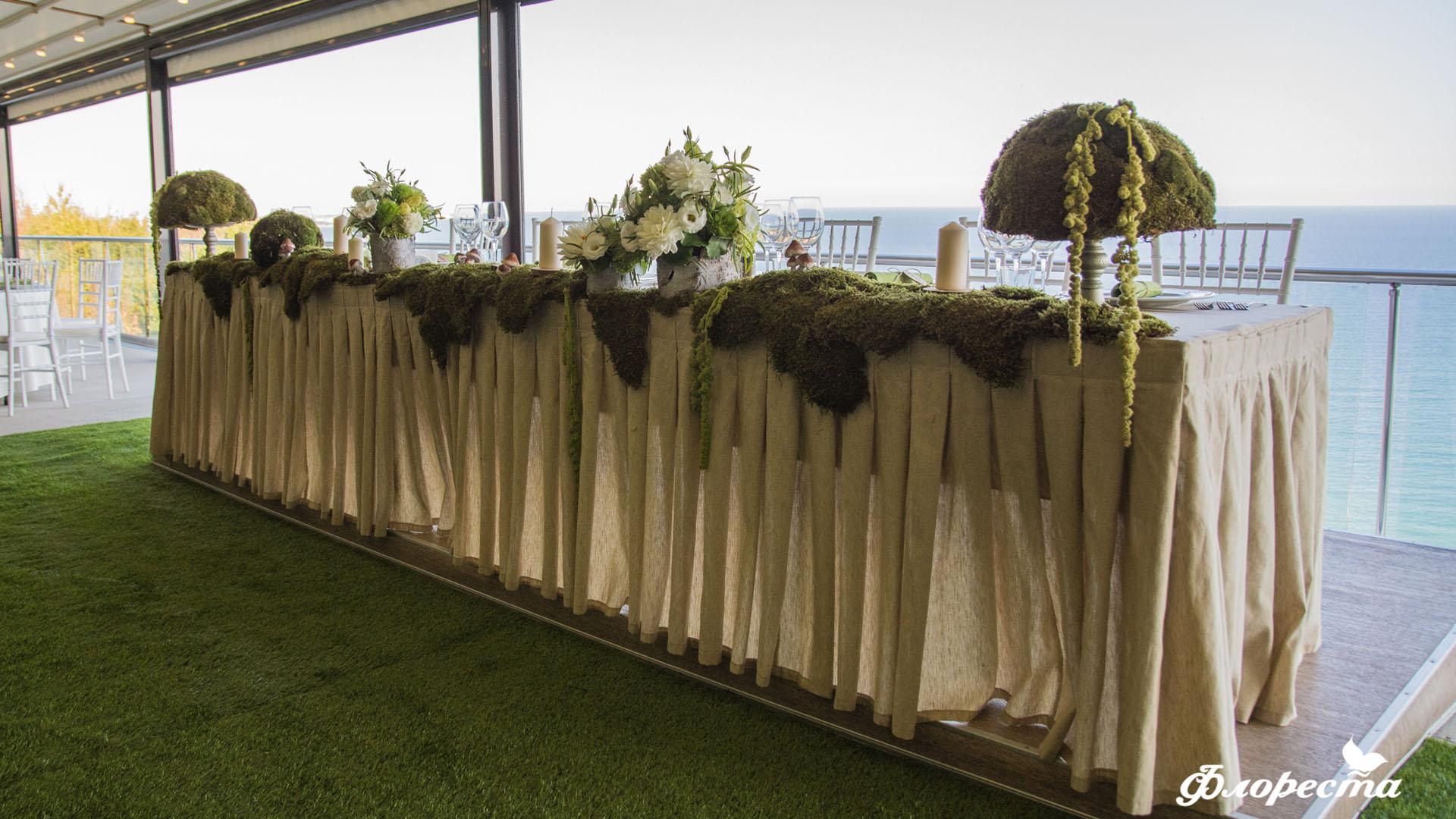 Сватбена декорация на масата на младоженците в горско зелено
